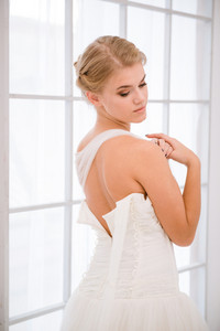 Bride putting on her white wedding dress