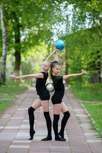 Gymnast girls posing with balls outdoor