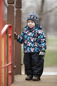 Cute little boy dressed in trendy winter clothes