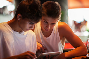 Young men using tablet computer in cafe