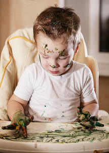 Creative little boy playing with finger paint