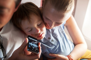 Child sleeping with music on cell phone in plane