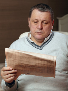 Portrait of senior man reading newspaper at home