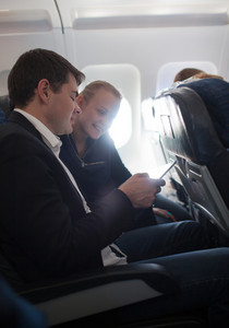 Young man and woman using cell phone in plane