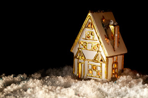 Little toy house covered with artificial snow