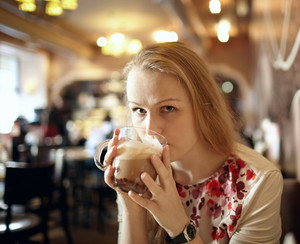 Girl is drinking latte in cafe