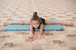 Little girl doing leg-split on the floor