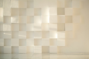 White painted concrete wall made of cubes with tiled floor
