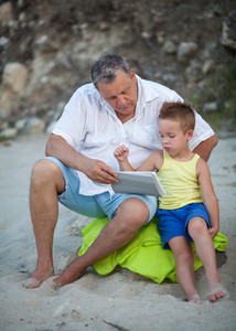 Grandfather and grandchild using pad on the beach