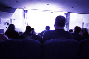People watching at bright screen in cinema
