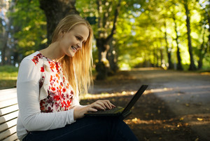 Young woman using her laptop in the park
