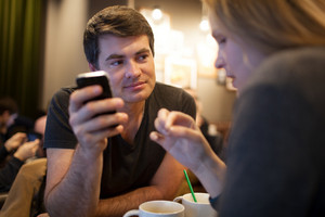 Man using mobile phone during meeting with girl in cafe