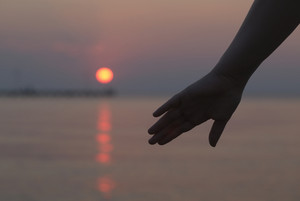 Womans hand silhouetted against a sunset