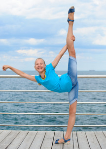 Smiling girl making stretching exercise by the sea