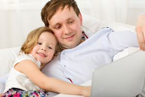 Happy dad and daughter with laptop