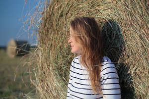 Young woman by the hay roll in the field