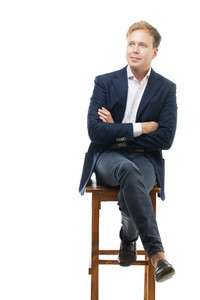 Young businessman sitting on high wooden chair