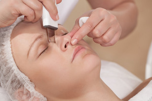 Face cleaning with ultrasonic equipment at beauty treatment salon