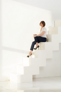 Elegant adult woman smiling while sitting on steps