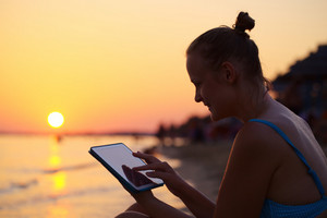 Smiling woman using pad on beach at sunset