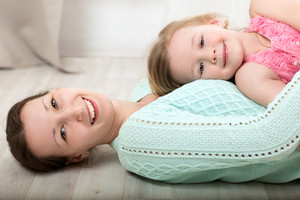 Smiling mother and daughter on the floor