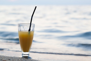 Glass of cocktail on beach near water