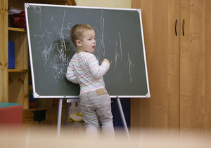 Creative little boy drawing on a chalkboard