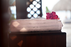 Pile of three white clean towels with flower on top