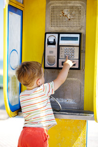 Young boy talking to the phone in a booth