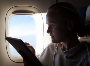 Woman sitting by illuminator in plane with touch pad