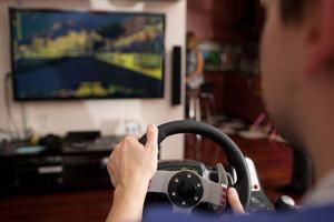 Man playing racing game with steering wheel simulator