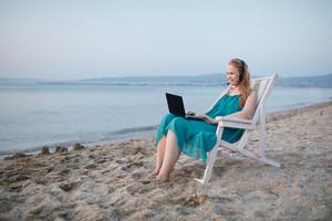 Woman talking skype at the beach
