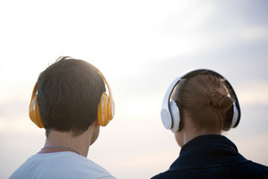 Young people in headphones enjoying music outdoor