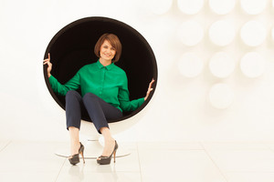 Elegant woman sitting on spherical chair