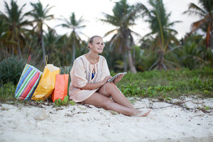 Woman relaxing with pad on beach after shopping