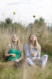 Two playful girls juggling outdoors