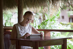 Smiling woman using tablet computer in cafe during vacation