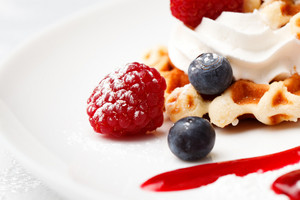 Golden waffle served with cream and berries