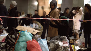 Syrian refugees listening to announcement at charity collecting point in copenhagen railroad station