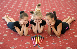 Three girls on the floor looking at indian clubs