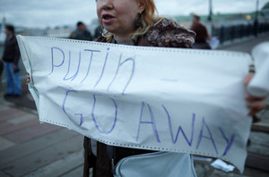 Woman holds a placard putin go away