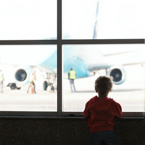 Boy looks at the plane at the airport