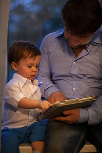 Man and little boy playing with tablet