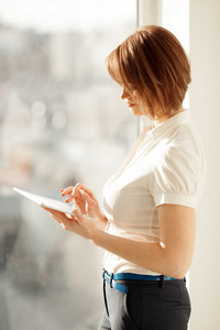Side view on woman working on tablet