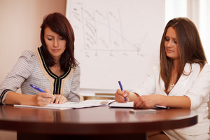 Two women taking notes at a business presentation