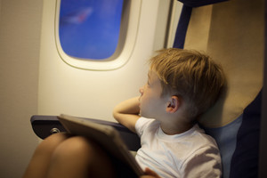 Boy in plane looking out illuminator with pad on lap