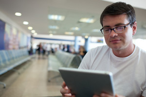 Man reading on tablet pc while waiting at the airport