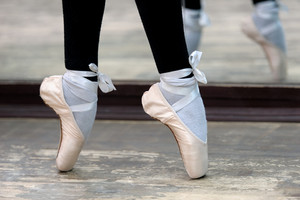 Close up view to ballerinas legs in pointes on wooden floor