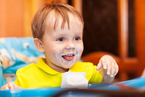 Happy child dirty with cream yoghurt