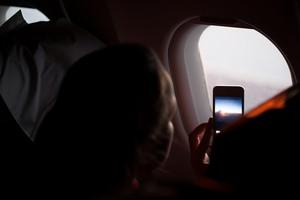Woman taking photographs through a cabin porthole